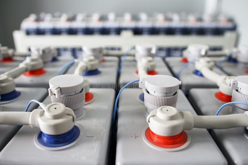 Bezpośredniego prądu bateria Accumulators baterie łączyli plus czerwony i minus błękit w elektrycznym składowym pokoju obrazy stock