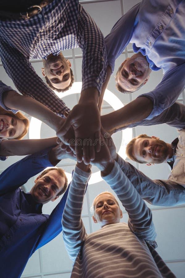 Bezpośrednio pod portretem biznesowi koledzy broguje ręki przy biurem zdjęcie stock