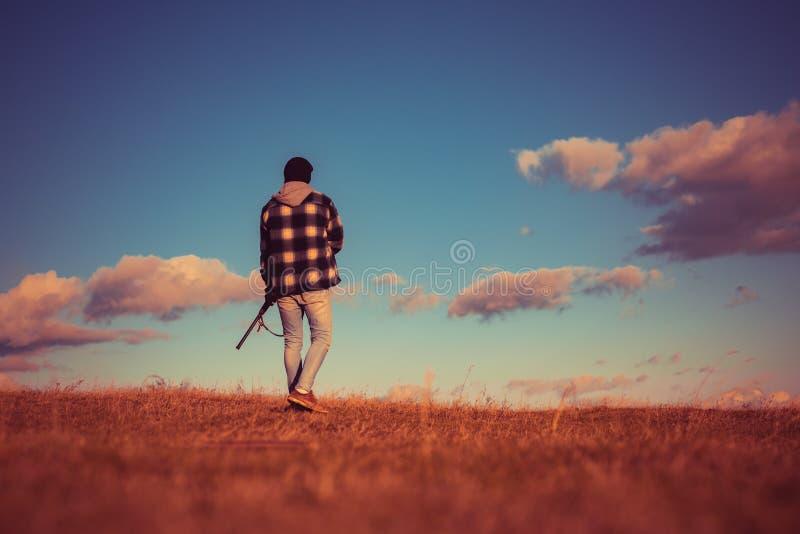 Bezprawny Łowiecki kłusownik w Lasowym Karabinowym myśliwym Sylwetkowym w Pięknym zmierzchu Jesień łowiecki sezon obraz stock