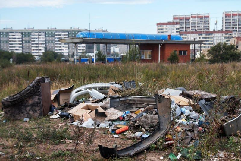 Bezprawny miasto usyp w suchej trawie blisko benzynowej stacji, fotografia royalty free