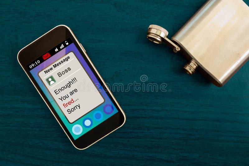 Bezrobocie problemów pojęcie Pracownika wygaśnięcia wiadomość na smartphone ekranie i pustej kolbie na stole Alkoholu nałóg i fotografia stock