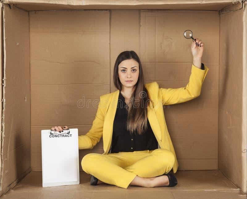 Bezrobotny bizneswoman trzyma lupe ostrożnie czytać przeciw fotografia stock