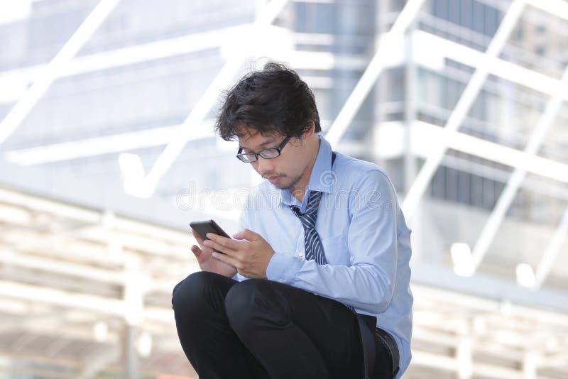 Bezrobotny młody Azjatycki mężczyzna patrzeje dla pracy w mobilnym mądrze telefonie przy miasta tłem Bezrobocia pojęcie obrazy royalty free