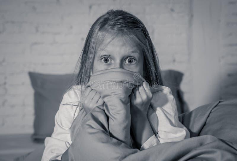 Bezsenna śliczna dziewczyna w strachu przy nocą chuje za koc przestraszoną zmrok i potwory zdjęcia royalty free