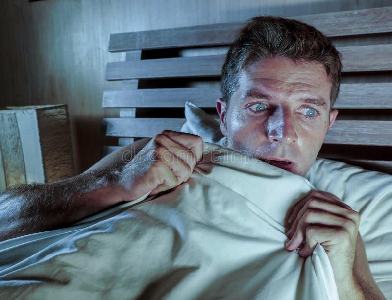 Bezsenny młodego człowieka lying on the beach w łóżku stresował się parano i okaleczał cierpienie koszmar przestraszącego horroru zdjęcie stock