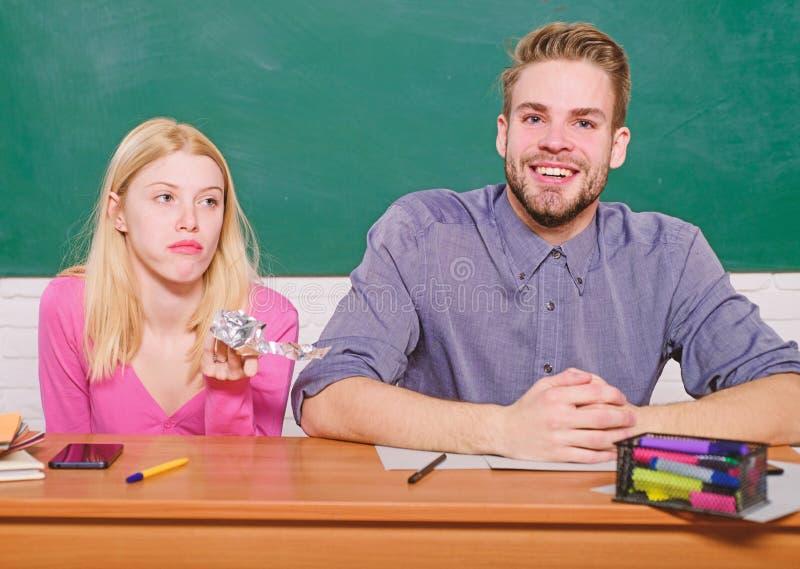 Beztroscy ucznie Cieszy? si? czas w szkole wy?sza Facet i dziewczyna siedzimy sal? lekcyjn? Studiowa? w szkole wy?szej lub uniwer obraz royalty free
