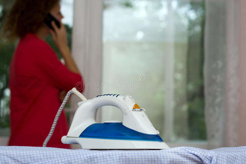 Beztroska dziewczyna opowiada na telefonie zapomina o żelazie na prasowanie desce obrazy royalty free