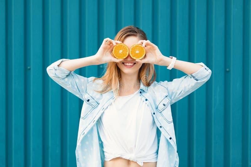 Beztroska młoda piękna dziewczyna używa dwa halfs na pomarańczach zamiast szkieł nad jej oczami obraz stock