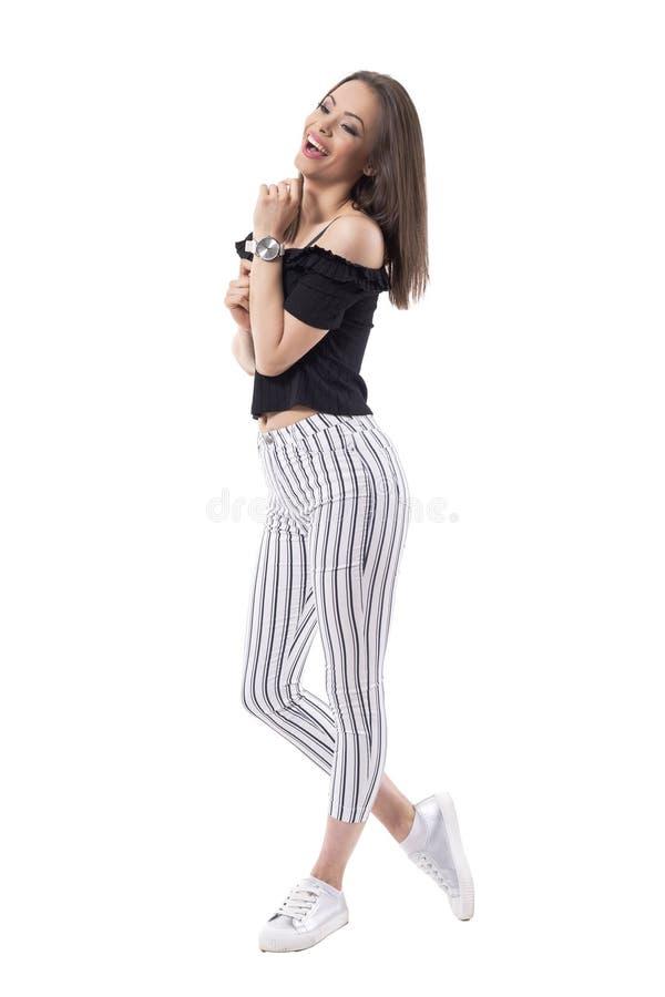 Beztroska szczęśliwa roześmiana młoda modna kobieta patrzeje daleko od w pasiastych spodniach Boczny widok zdjęcie royalty free