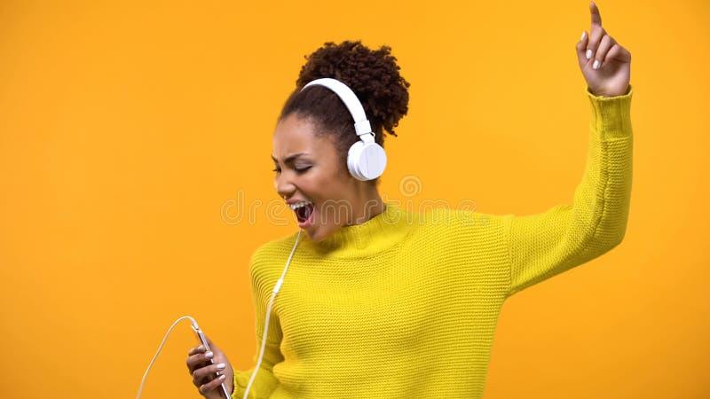 Beztroski żeński millennial śpiew na jaskrawym tle jest ubranym hełmofony, zabawa zdjęcie stock