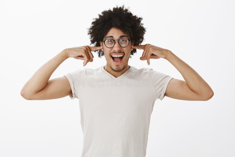 Beztroski atrakcyjny śmieszny latynoski samiec model z kędzierzawym włosy, końcowymi ucho z, palcami wskazującymi i krzyczeć, być zdjęcia royalty free