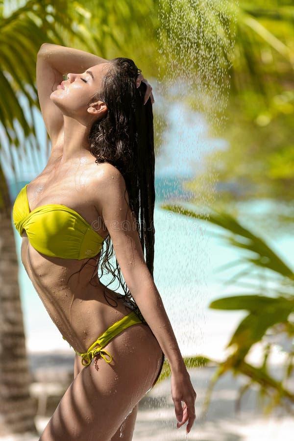 Beztroskiego mokrego seksownego bikini wzorcowa cieszy si? plenerowa tropikalna prysznic Pi?kna kobieta z d?ugie w?osy natryskiwa zdjęcia stock