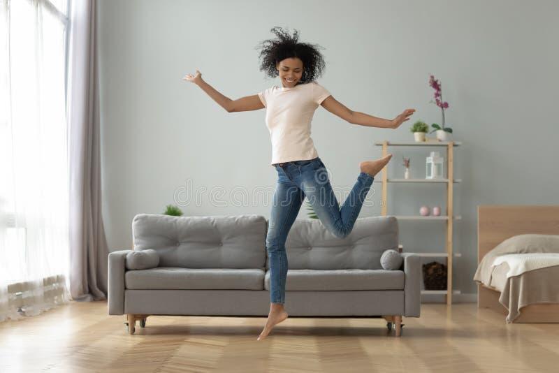 Beztroskiej radosnej afrykańskiej dziewczyny skokowy dancingowy samotny w domu zdjęcia royalty free