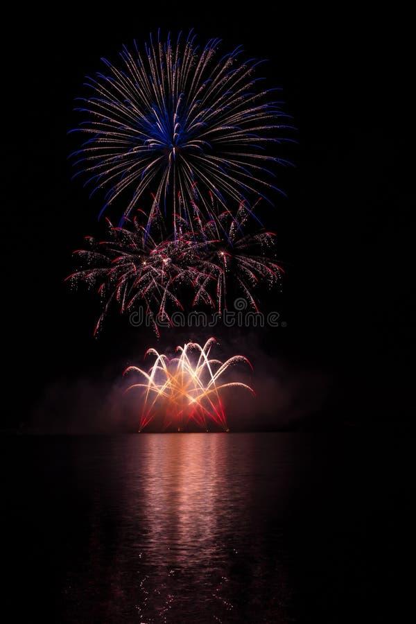 BGold, czerwień, błękitne gwiazdy i fontanna od bogatych fajerwerków nad Brno tamą z jeziornym odbiciem, obraz stock