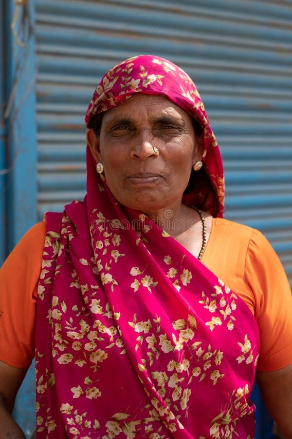 Bhadarsa, Уттар-Прадеш/Индия - 2-ое апреля 2019: Женщина представляет для фото рядом с ее фруктовой лавкой стоковая фотография rf