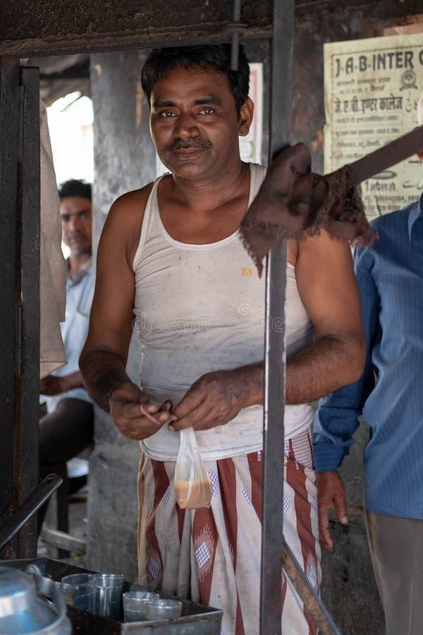 Bhadarsa, Уттар-Прадеш/Индия - 2-ое апреля 2019: Местный человек chai представляет для фото во время спешкы утра стоковое фото