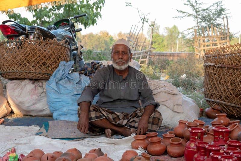 Bhadarsa, Uttar Pradesh/Índia - 3 de abril de 2019: Um homem levanta para uma foto ao vender a cerâmica em um festival que cerca  fotos de stock