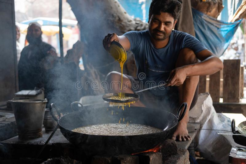 Bhadarsa, Uttar Pradesh / India - April 2, 2019: A man frys up jalebi street side in Bhadarsa. royalty free stock photography