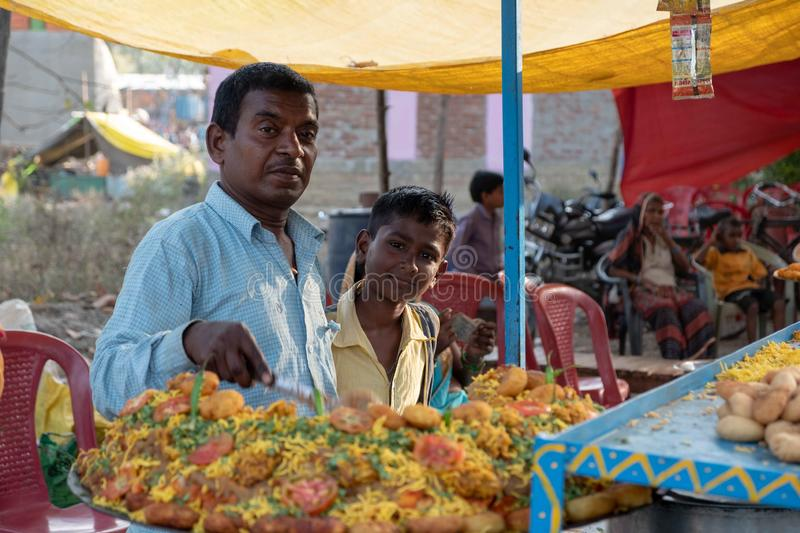 Bhadarsa, Uttar Pradesh / India - April 3, 2019: A man poses for a photo with his son while making street food at a festival surro royalty free stock photo
