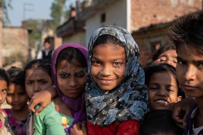 Bhadarsa, Uttar Pradesh/la India - 2 de abril de 2019: Un grupo de muchachas presenta para una foto fuera de su pueblo fotografía de archivo