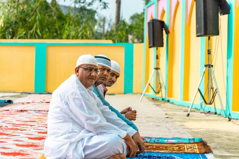 Asian Muslim devotees sitting in a row getting ready for Eid Prayers. stock photos