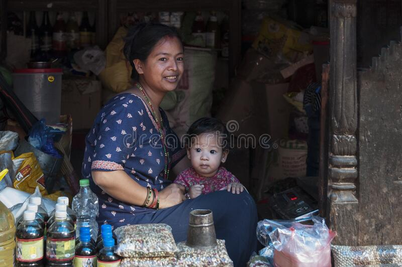 Unidentified Nepalese Newari woman with her child in a haberdashery in Bhaktapur, listed as a World Heritage by UNESCO royalty free stock image