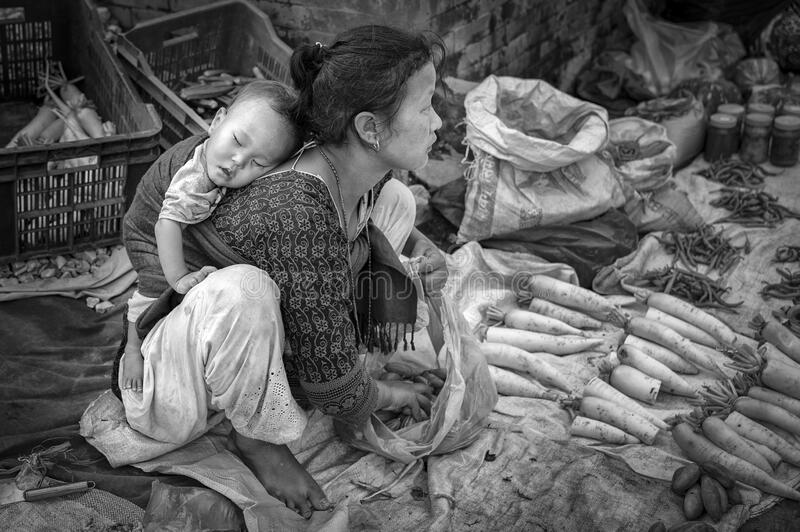 Unidentified Nepalese woman with a little child selling vegetables in Bhaktapur, listed as a World Heritage by UNESCO stock photo
