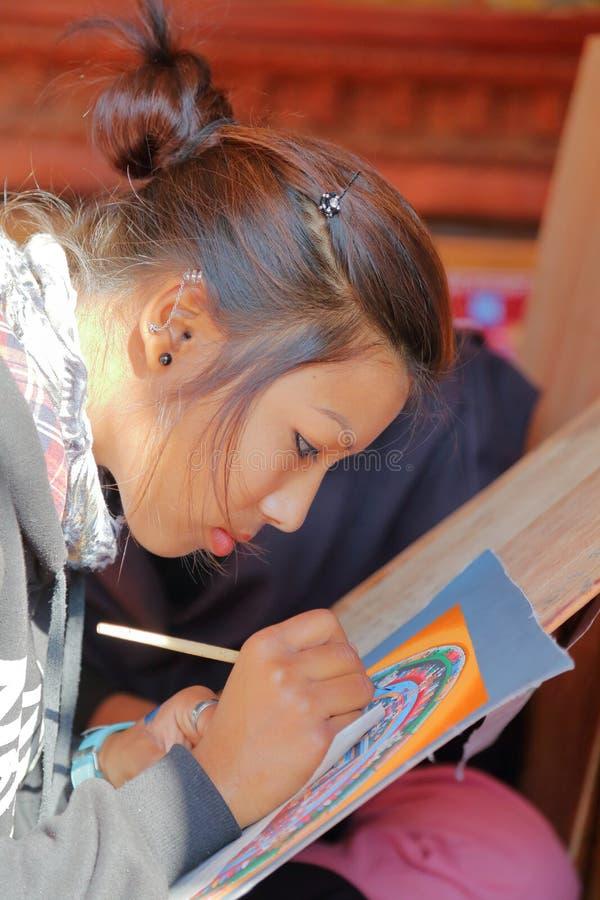 BHAKTAPUR, NEPAL - 29 DE DICIEMBRE DE 2014: Un artista local que pinta a un tibetano tradicional Thangka foto de archivo