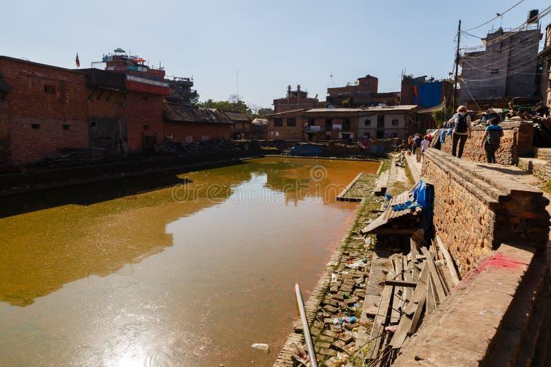 BHAKTAPUR NEPAL - 15 DE NOVIEMBRE DE 2016: Casas newar nepalesas tradicionales cerca de la charca verde en Bhaktapur, Nepal imágenes de archivo libres de regalías