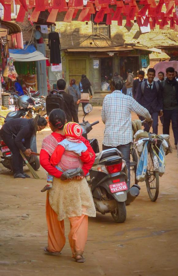 Everyday life in Bhaktapur, Nepal. Woman with child, man with bicycle, students in uniform. Bhaktapur, Nepal - 11/21/2017: Everyday life, young woman carrying a stock images