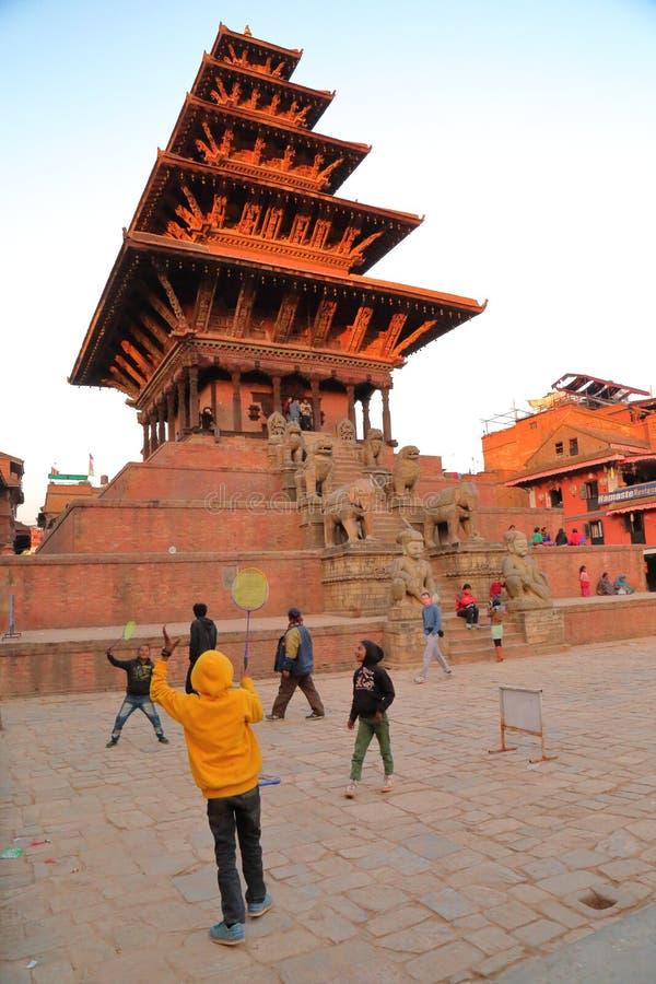 BHAKTAPUR NEPAL, GRUDZIEŃ, - 28, 2014: Dzieci bawić się Badmington przy zmierzchem przed Bhairabnath świątynią przy Taumadhi Tole zdjęcia stock