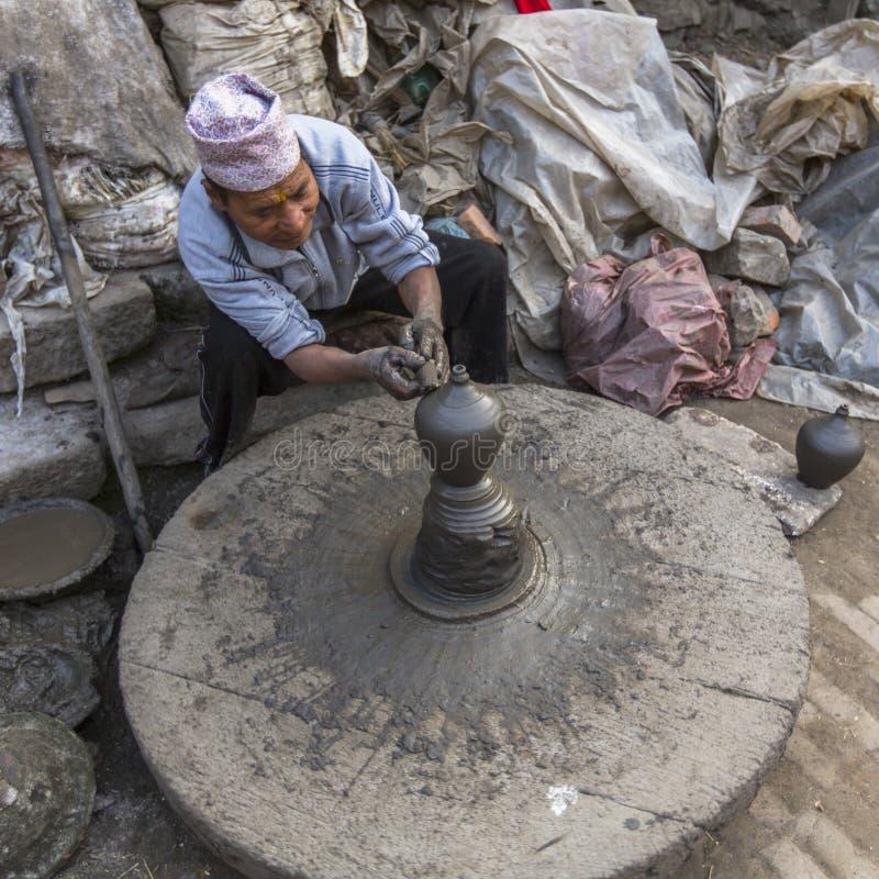 BHAKTAPUR, NEPAL - hombre nepalés que trabaja en su taller de la cerámica imagenes de archivo