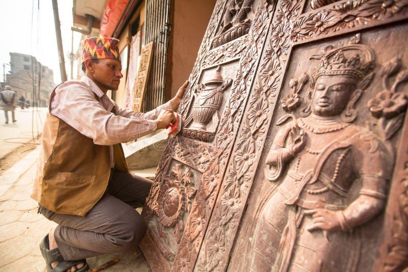 BHAKTAPUR, NEPAL - homem nepalês não identificado que trabalha em sua oficina de madeira imagem de stock