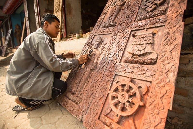 BHAKTAPUR, NEPAL - homem nepalês não identificado que trabalha em sua oficina de madeira foto de stock