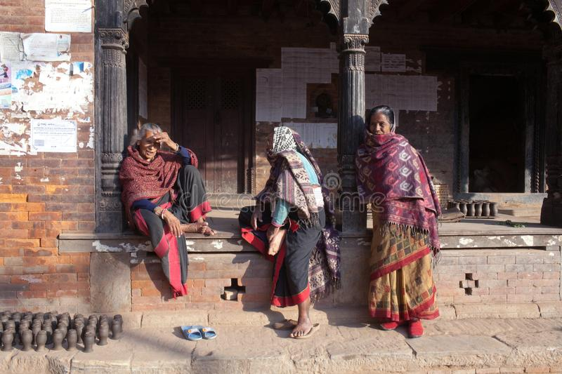 Women chat together at Durbar Square in Bhaktapur, Nepal. BHAKTAPUR, NEPAL - JANUARY 23, 2017: Nepalese women chat together at Durbar square royalty free stock images