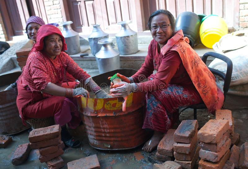 Nepalese women working hard in building site. BHAKTAPUR, NEPAL - JANUARY 23, 2017: Nepalese women working hard in building after the earthquake damage in royalty free stock image