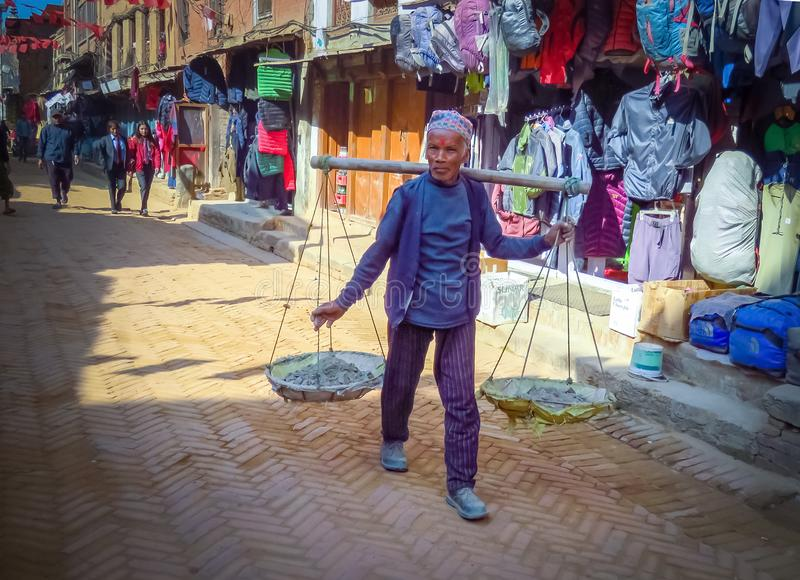 Man in shopping street of Bhaktapur, Nepal. Bhaktapur, Nepal - 11/21/2017 : Man with wooden carrying pole and wicker baskets walking along the shops in the stock image