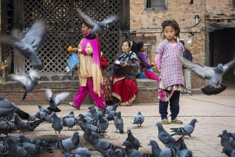 Bhaktapur, Nepal - November 11, 2017. People surrounded by pigeons relaxing in a temple of Bhaktapur, Nepal, stock photos