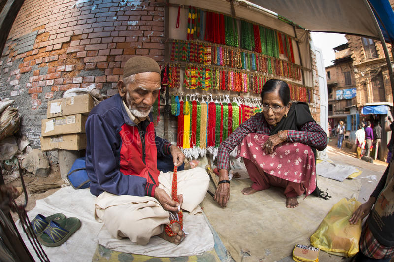 BHAKTAPUR, NEPAL - NOVEMBER 20: People working and selling goods royalty free stock photo