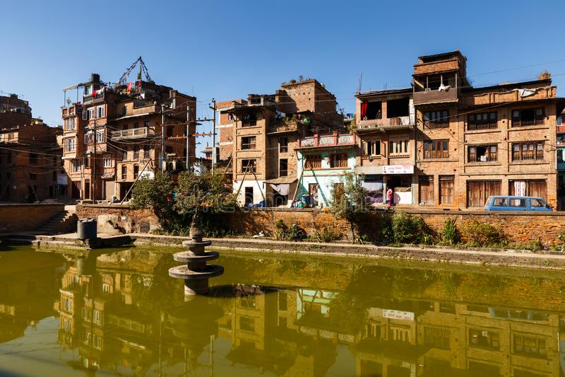 BHAKTAPUR NEPAL - NOVEMBER 15, 2016: Traditionella nepalese newar hus nära det gröna dammet i Bhaktapur, Nepal royaltyfri bild