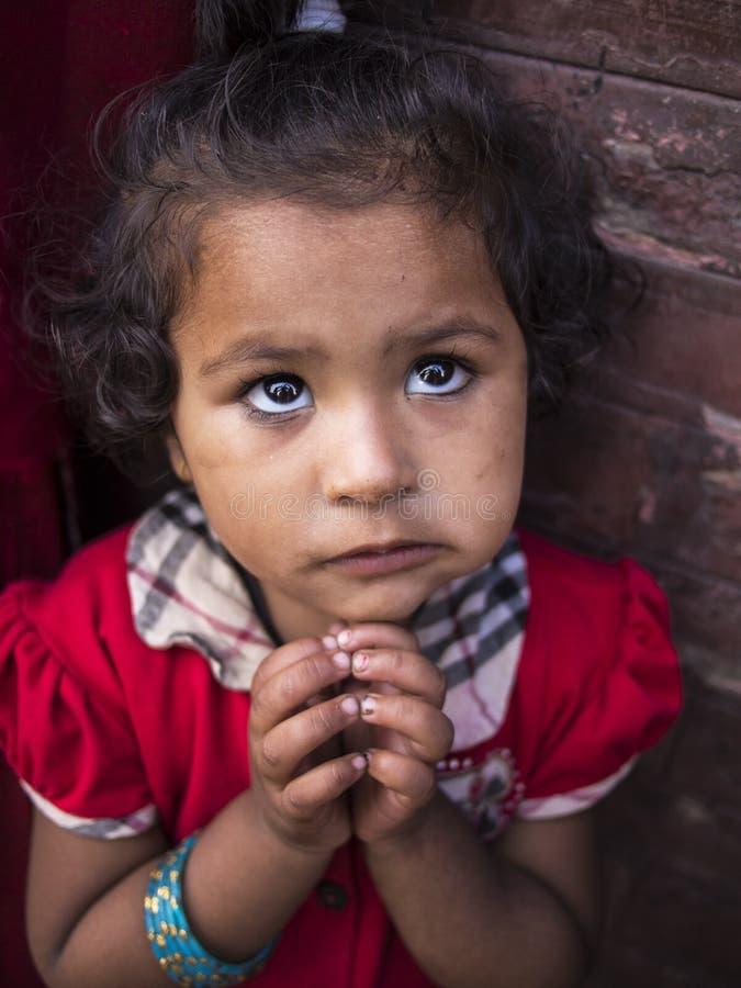 BHAKTAPUR, NEPAL-OCT 14, 2012: het meisje vraagt om t royalty-vrije stock afbeelding