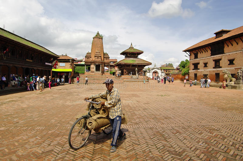 BHAKTAPUR,NP - CIRCA AUGUST 2012 - Man with bicycle in Durbar sq royalty free stock photography