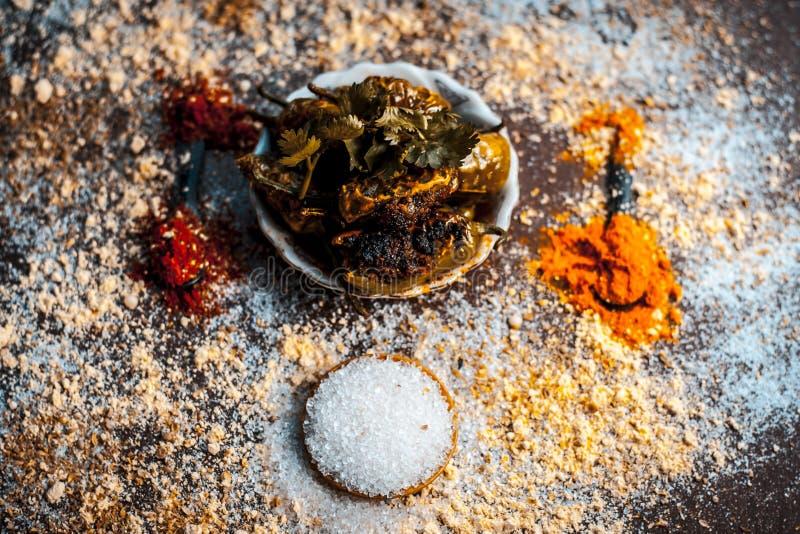Bhareli mirchi eller välfyllda chilies på träyttersida i en exponeringsglasplatta tillsammans med några kryddor och hela rå ingre arkivbilder