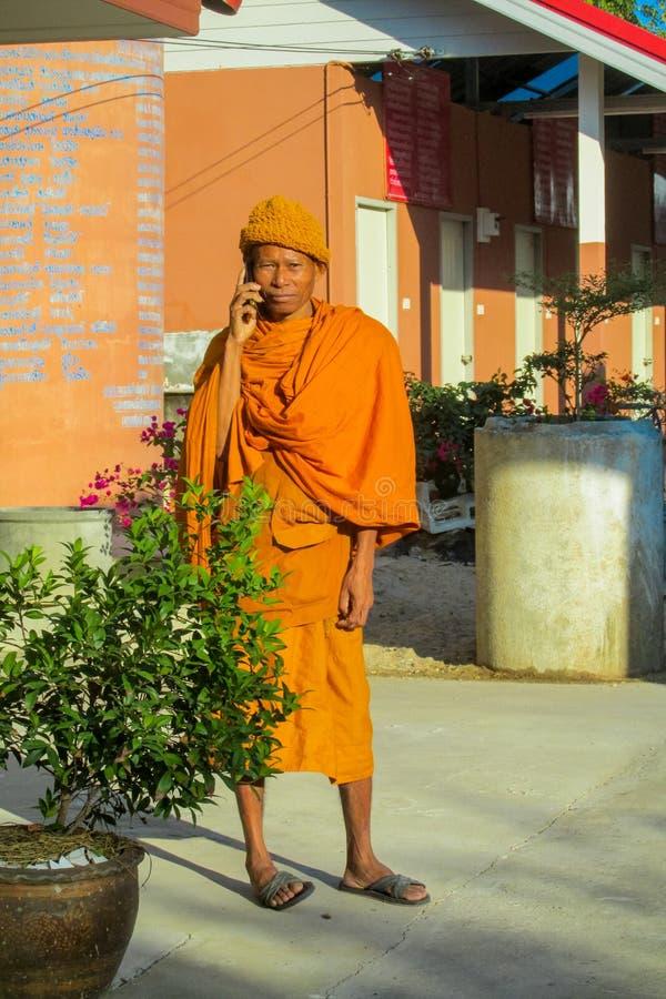 Bhikkhu de moine bouddhiste dans le wat de temple de la Thaïlande parlant le téléphone portable image libre de droits