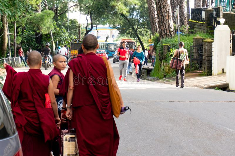 Bhuddhist monks walking on teh street with umbrellas in the monastries of Dharamshala royalty free stock photography