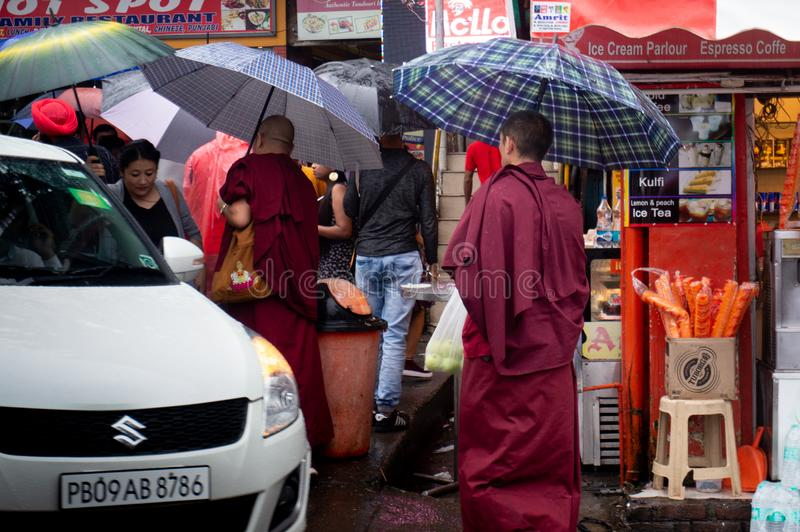 Bhuddhist monks walking on teh street with umbrellas in the monastries of Dharamshala royalty free stock image