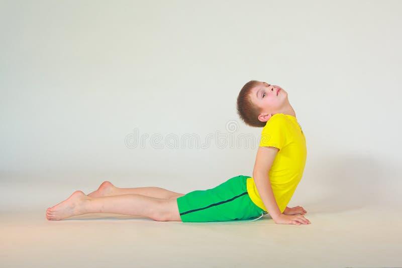 Bhudzhangasana yoga. Little boy doing yoga on white background royalty free stock images