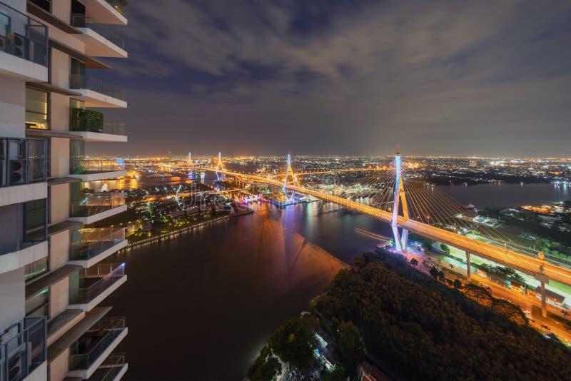 Bhumibol桥梁、昭披耶河和大厦在晚上 免版税库存图片