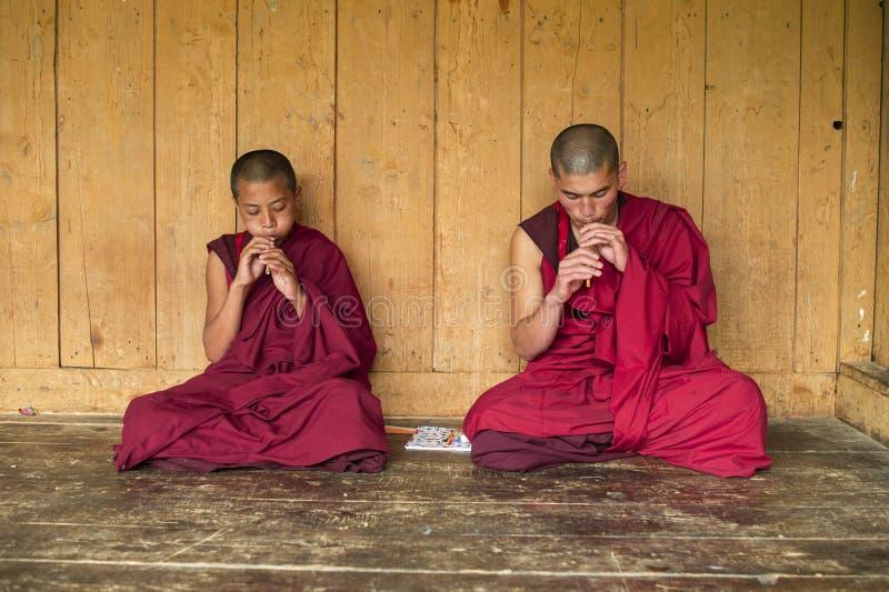 Bhutanesiska buddistiska novismunkar som sitter och spelar flöjten, Bhutan arkivbilder