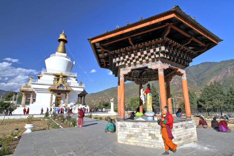 Bhutanesiskt folk i traditionell klänning med det tibetana bönhjulet fotografering för bildbyråer
